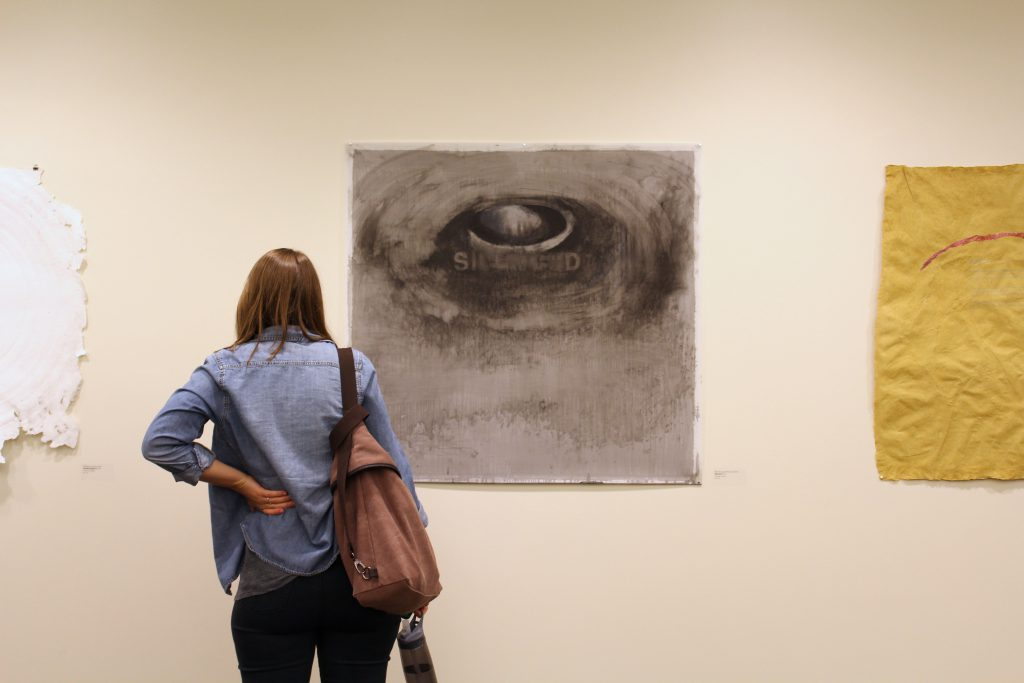 Photograph of a woman, seen from behind, standing in front of a drawing.