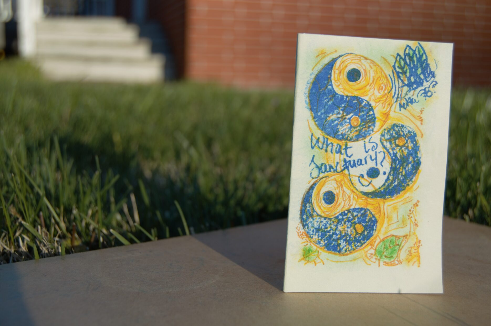 "A zine, ""What is Sanctuary,"" is pictured on a grassy background."