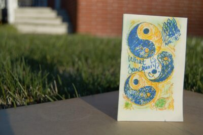 """A zine, """"What is Sanctuary,"""" is pictured on a grassy background."""
